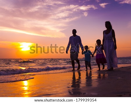 Family Walking on The Beach at Sunset - stock photo
