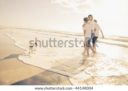 Family walking on the beach with dog - stock photo