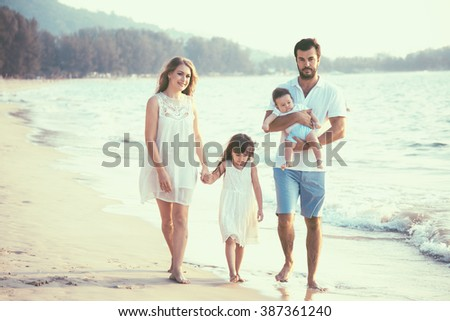 Family walking on the evening beach during sunset. Children with parents. - stock photo