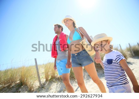 Family walking to the beach on a sunny day - stock photo