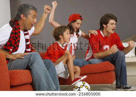 Family watching a sports match on TV. - stock photo