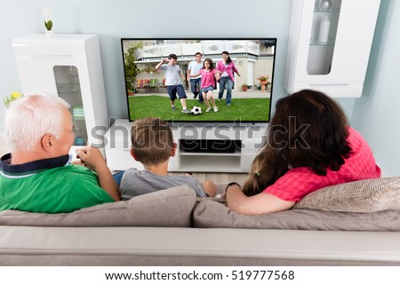 Family Watching Football Game On TV With Kids