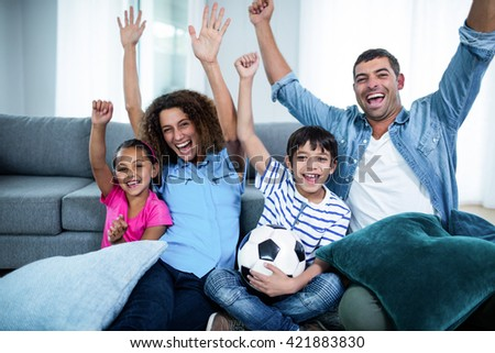 Family watching match on television at home - stock photo
