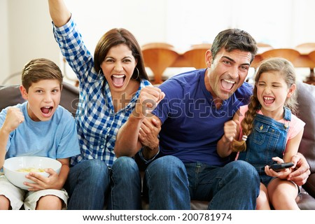 Family Watching Soccer Celebrating Goal - stock photo