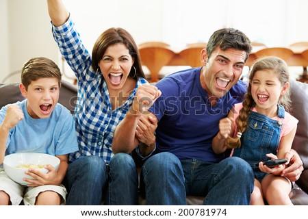 Family Watching Soccer Celebrating Goal - stock photo