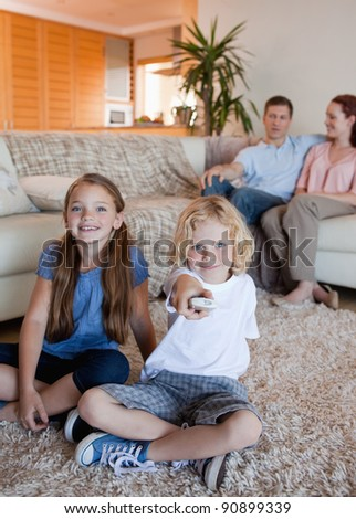 Family watching television in the living room together - stock photo