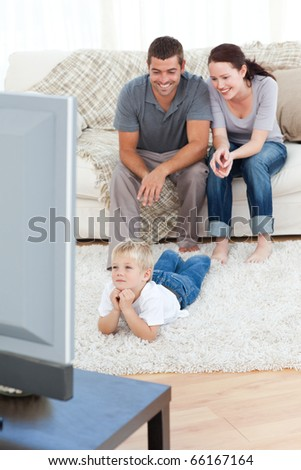 Family watching television together at home