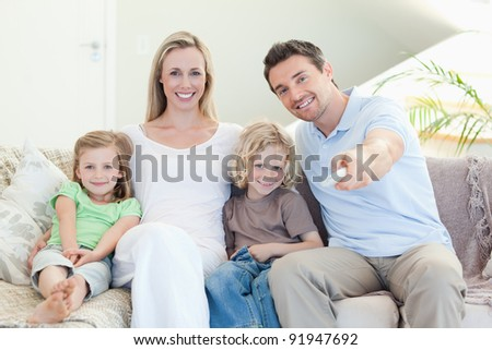 Family watching television together on the sofa - stock photo