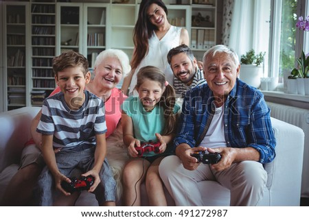 Family watching the kids playing video game at home