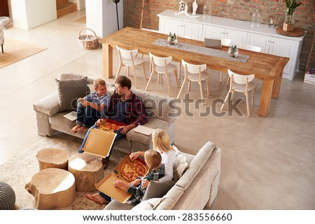 Family watching TV and eating pizza - stock photo