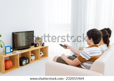 Family watching tv at home - stock photo
