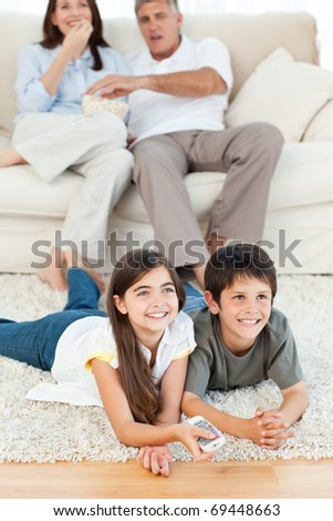 Family watching tv in the living room at home - stock photo