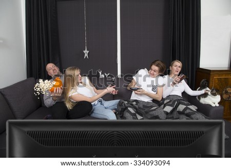 Family watching tv together, siblings fighting over the remote control - stock photo