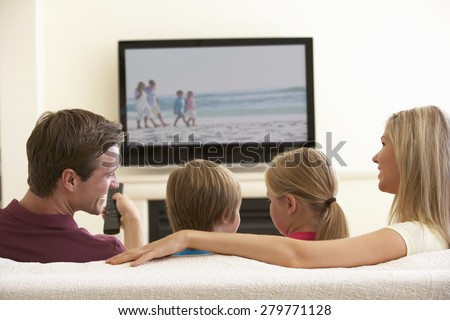Family Watching Widescreen TV At Home - stock photo