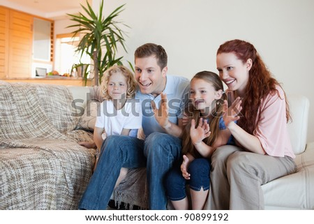 Family waving their hands in the living room