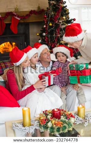 Family wearing christmas hat while holding presents at home in the living room - stock photo