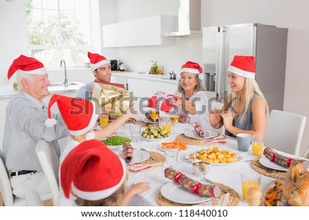 Family wearing santa hats swapping christmas presents at dinner table - stock photo