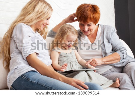 Family wiht tablet computer at sofa. Mother, grandmother and little girl at home on sofa. Generation - stock photo