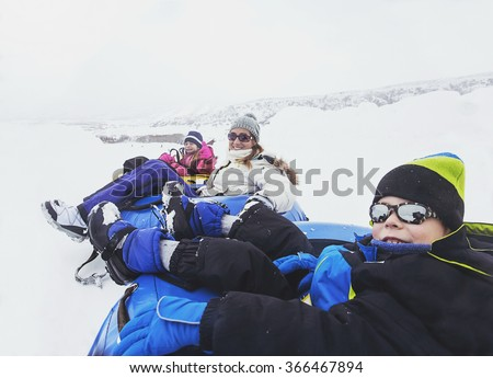 Family winter fun. Kids and Mom Sledding downhill together and playing in snow - stock photo
