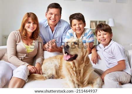 Family with a dog posing on sofa