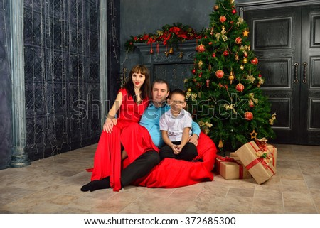 Family with a gift near a fir-tree - stock photo