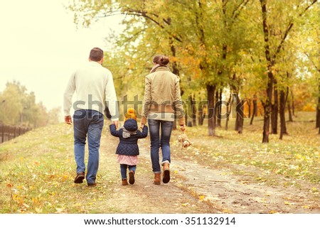 Family with a small daughter walk in autumn park - stock photo