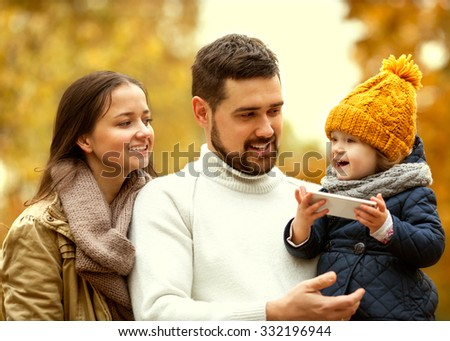 Family with a small daughter walk in autumn park with telephone