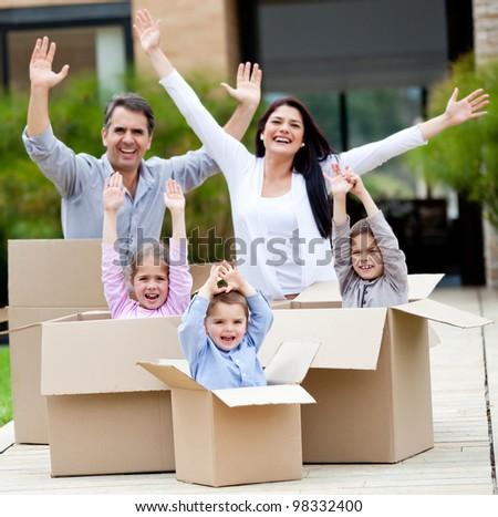 Family with arms up celebrating they are moving home - stock photo