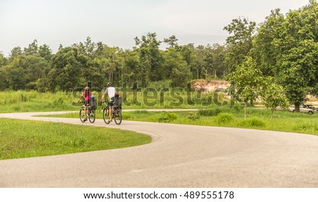 Family with baby and girl child having a weekend excursion on their bikes on a summer day in beautiful landscape