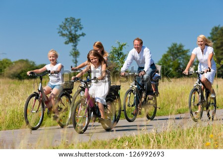 Family with baby and three girls having a weekend excursion on their bikes on a summer day in beautiful landscape