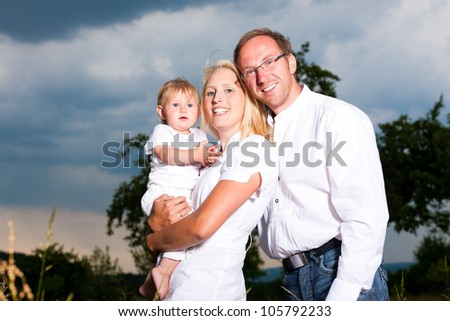 Family with baby child standing in a meadow � father, mother, child