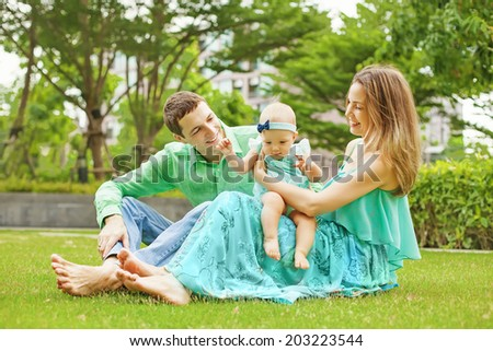 Family with baby in park - stock photo