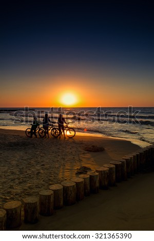 Family with bicycles on the Baltic Sea at sunset