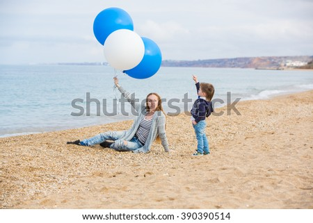 Family with big balloons playing on the beach