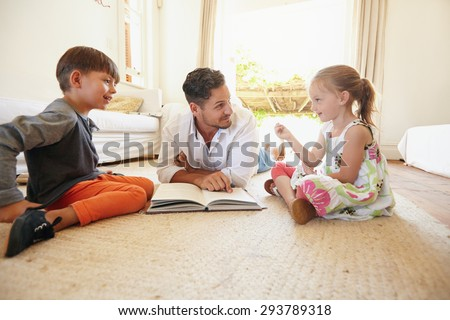 Family with book sitting on floor with little girl talking to his father and brother. Father with his little boy and girl at home. - stock photo