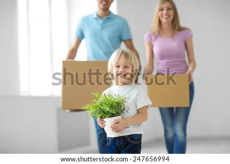 Family with boxes at home - stock photo