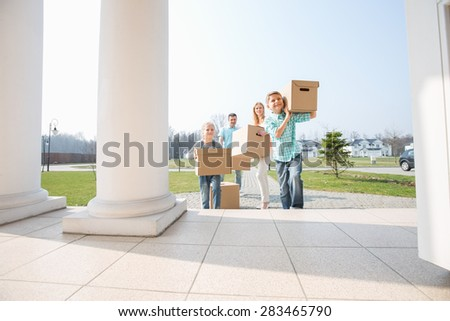 Family with cardboard boxes entering into new house - stock photo