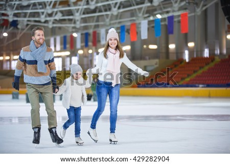 Family with child at ice-skating rink - stock photo