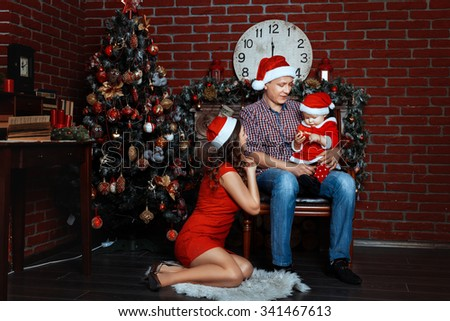 Family with child near Christmas tree. The child sits in the hands of dads