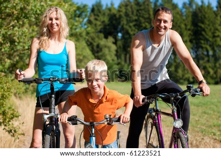 Family with child on their bikes on a summer day in sport outfit, they are exercising - stock photo