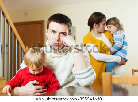 Family with children having quarrel at home in the hall - stock photo