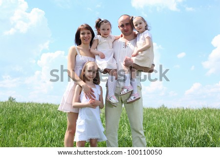 family with children in summer day on the meadow - stock photo