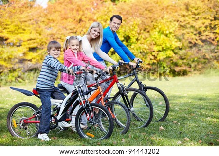 Family with children on bikes in the park - stock photo