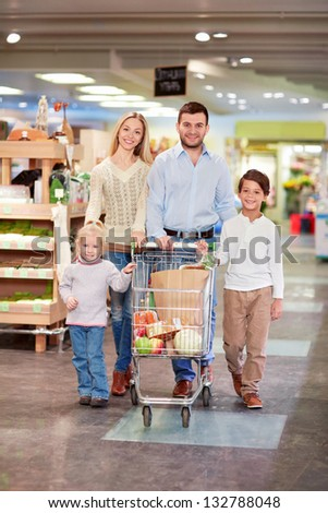 Family with children products with a cart in the store - stock photo