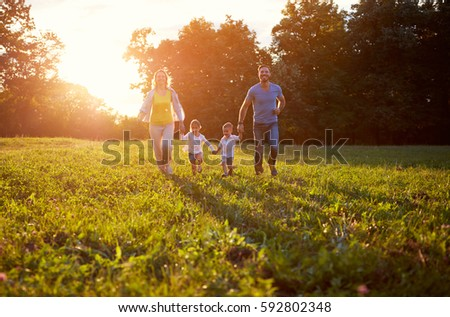 Family with children run together in nature