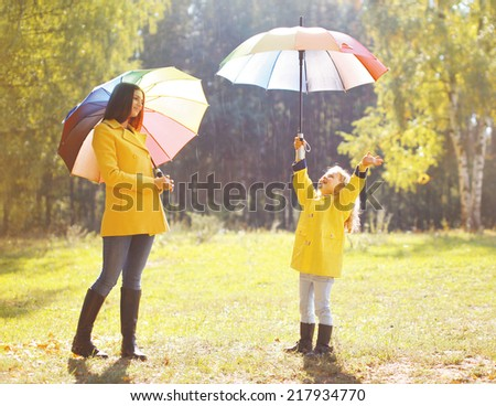 Family with colorful umbrella having fun enjoying weather in autumn day - stock photo