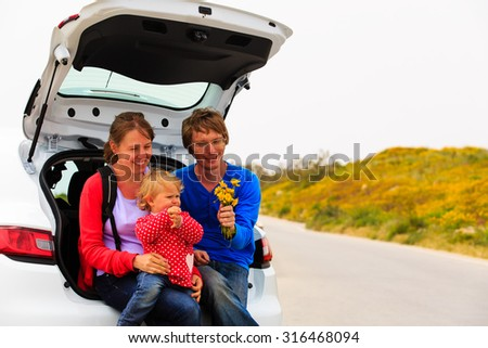 family with cute little daughter travel by car in nature