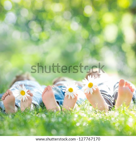 Family with daisy flowers lying on green grass against spring blurred background - stock photo