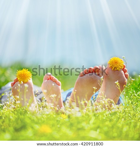 Family with dandelion  flowers lying on green grass in sunny day. Concept happy childhood. - stock photo