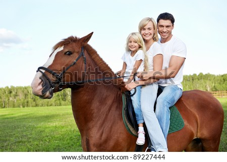 Family with daughter on a horse - stock photo